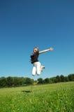 Ragazza felice giovane di salto Immagini Stock