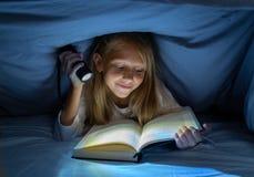 Ragazza felice graziosa che legge un libro nell'oscurità che si nasconde sotto il piumino a letto con luce istantanea fotografie stock