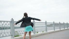 Ragazza felice nelle passeggiate e nelle pose divertenti del vestito alla macchina fotografica sulla banchina video d archivio