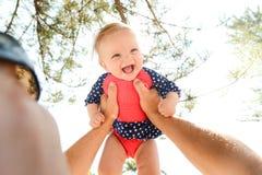 Ragazza felice nelle sue armi dei padri Fotografie Stock