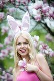 Ragazza felice o donna sveglia con le orecchie del coniglietto alla magnolia fotografia stock