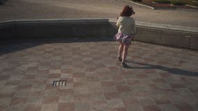 Ragazza felice pazza che balla in un rivestimento d'uso del biege della fontana vuota del palazzo ed in una gonna viva variopinta stock footage
