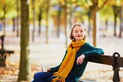 Ragazza felice in sciarpa gialla che cammina nel parco di autunno immagine stock