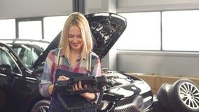 Ragazza felice sorridente che gode del lavoro al garage del te archivi video