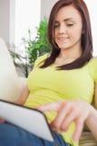 Ragazza felice sorridente che per mezzo di un pc della compressa che si siede su un sofà Fotografia Stock