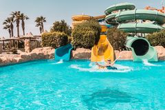 Ragazza felice su un acquascivolo nello stagno, divertendosi durante le vacanze estive in un bello parco dell'acqua fotografie stock
