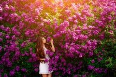 Ragazza felice sul fondo dei fiori Fotografia Stock