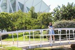 Ragazza felice sul ponte vicino al giardino della città delle arti e delle scienze a Valencia Immagine Stock