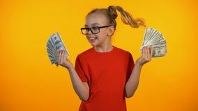 Ragazza felice sveglia che mostra i mazzi di contanti del dollaro, concessione di conquista del wunderkind, reddito archivi video