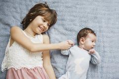 Ragazza felice sveglia che tiene suo fratello del neonato Fondo grigio Neonato grazioso in vestiti blu immagine stock libera da diritti