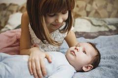Ragazza felice sveglia che tiene suo fratello del neonato Fondo grigio Neonato grazioso in vestiti blu fotografia stock