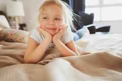 Ragazza felice sveglia del bambino che si siede sul letto in pigiama Fotografia Stock Libera da Diritti