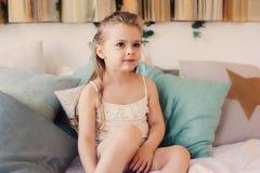 Ragazza felice sveglia del bambino che si siede sul letto in pigiama Bambino che gioca nel paese Immagine Stock