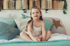 Ragazza felice sveglia del bambino che si siede sul letto in pigiama Bambino che gioca nel paese Immagine Stock Libera da Diritti
