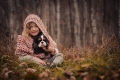 Ragazza felice sveglia del bambino con il suo cane sulla passeggiata accogliente di autunno in foresta Fotografie Stock Libere da Diritti