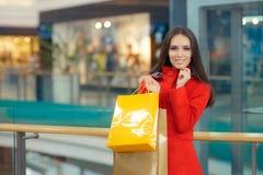 Ragazza felice in un acquisto rosso del cappotto in un centro commerciale immagini stock libere da diritti