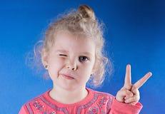 Ragazza felice in una posa di vittoria ragazza che mostra il segno di pace e winkin Immagine Stock