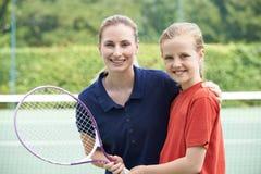Ragazza femminile di Giving Lesson To della vettura di tennis immagine stock