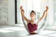Ragazza flessibile che fa posizione di yoga in una palestra Fotografie Stock