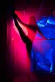 Ragazza flessibile che posa in una siluetta del night-club che solleva il suo vantaggio Immagine Stock