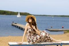 Ragazza floreale con il cappello che si siede sulla spiaggia fotografie stock