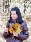 Ragazza in foglie di acero della holding della foresta di autunno Fotografie Stock