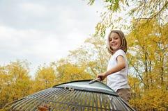 Ragazza in foglie di rastrellamento di autunno Immagine Stock