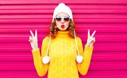 Ragazza fresca che soffia le labbra rosse che portano un cappello giallo tricottato variopinto del maglione immagine stock
