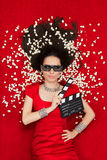 Ragazza fresca con i vetri del cinema 3D, il popcorn e direttore Clapboard Immagine Stock