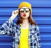 Ragazza fresca dei pantaloni a vita bassa in occhiali da sole e vestiti variopinti divertendosi sopra il blu Fotografia Stock