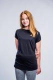 Ragazza in ghette nere di forma fisica e della maglietta, colpo dello studio Fotografia Stock Libera da Diritti