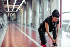 Ragazza giù per fare i laccetti alla palestra di forma fisica prima dell'allenamento corrente di esercizio Immagini Stock