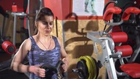 Ragazza in ginnastica Addestramento del peso Lavoro sui muscoli della parte posteriore Donne che risolvono sul vogatore in palest archivi video