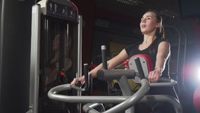 Ragazza in ginnastica Addestramento del peso Lavoro sui muscoli della parte posteriore Donne che risolvono sul vogatore in palest video d archivio