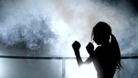 Ragazza, giovane donna che fa pugilato di ombra, kickboxing siluetta contro il fumo stock footage