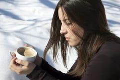 Ragazza/giovane donna che pensa sopra una tazza di caffè Fotografie Stock Libere da Diritti