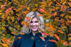 Ragazza grassa con il bello sorriso nel fogliame di autunno fotografie stock