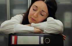 Ragazza graziosa addormentata sulle cartelle con i rapporti Fotografie Stock