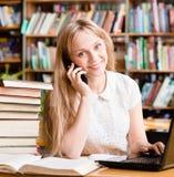 Ragazza graziosa in biblioteca che scrive sul computer portatile e che parla sul telefono Fotografie Stock Libere da Diritti