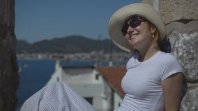 Ragazza graziosa in cappello ed occhiali da sole che ammirano la vista del mare e natura che si siede vicino alle pareti di pietr stock footage