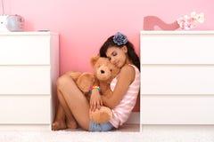 Ragazza graziosa che abbraccia giocattolo molle con amore Fotografie Stock