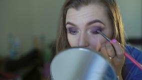 Ragazza graziosa che applica trucco dell'occhio con le ombre 4K stock footage