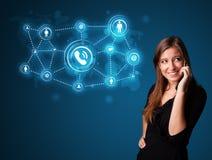Ragazza graziosa che fa telefonata con le icone della rete sociale Fotografia Stock Libera da Diritti