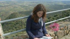 Ragazza graziosa che ha libro di lettura e di resto durante il viaggio backpacking alle montagne archivi video