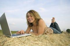 Ragazza graziosa che lavora al computer portatile Immagini Stock Libere da Diritti