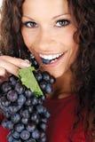 Ragazza graziosa che mangia uva fotografia stock