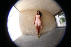 Ragazza graziosa che posa contro la parete, fisheye fotografie stock