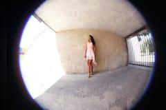Ragazza graziosa che posa contro la parete, fisheye fotografia stock libera da diritti