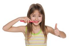 Ragazza graziosa che pulisce i suoi denti Fotografia Stock