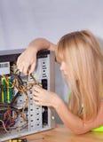 Ragazza graziosa che ripara computer Fotografia Stock